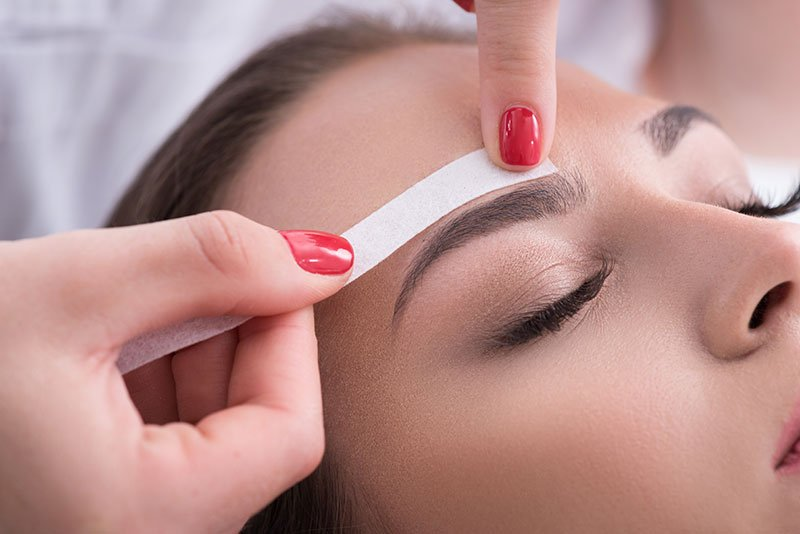 Image of a beautician carrying out an eyebrow waxing treatment
