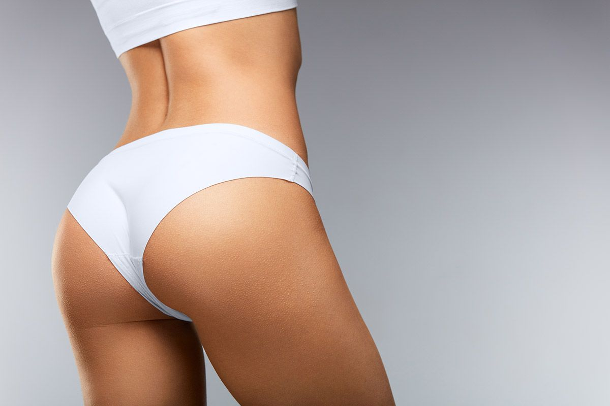 Picture of a lady's back in white underwear, showing the area from the top of her torso to her thighs
