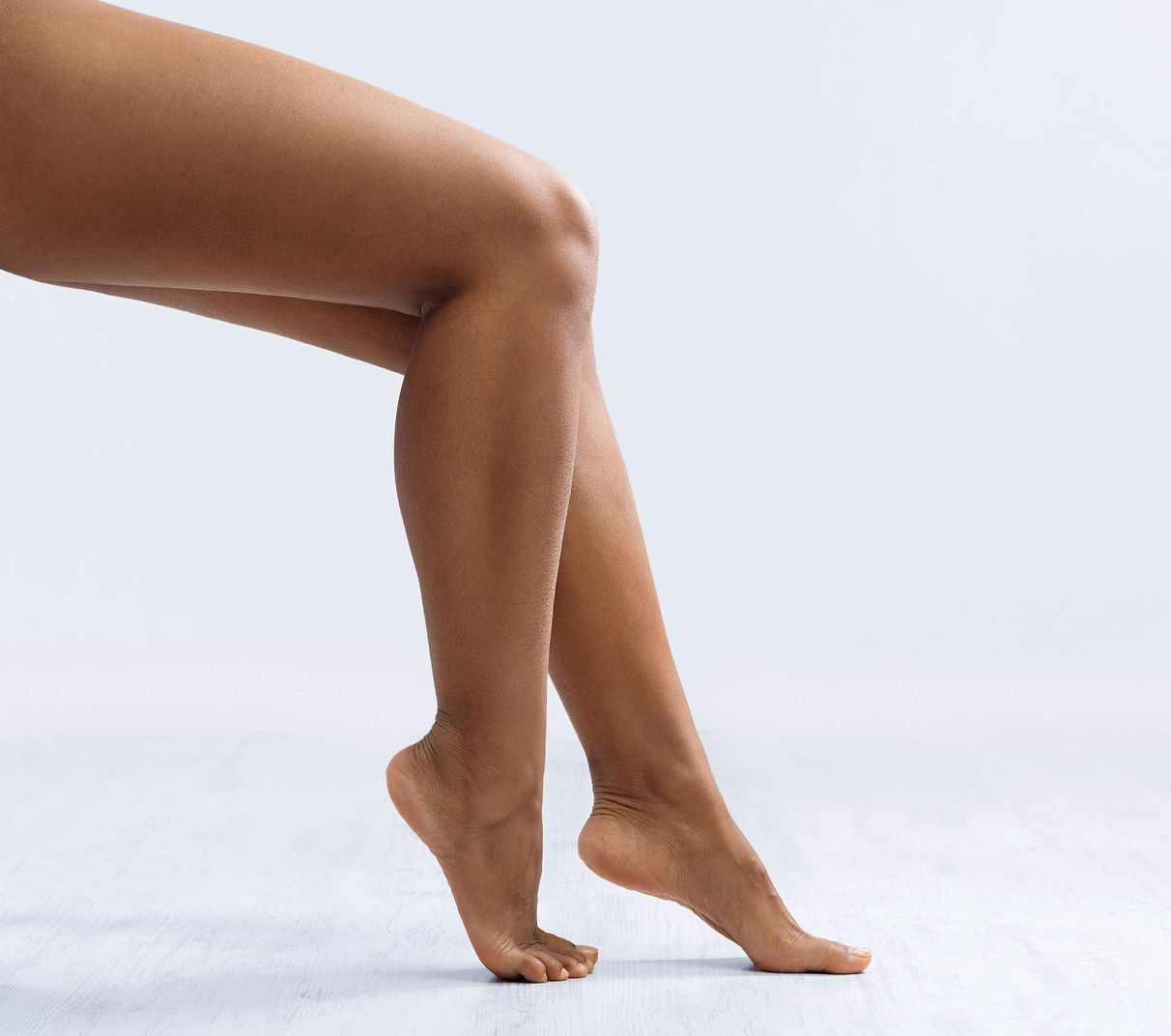 Picture of legs from a person sitting down, barefoot, showing only below the knee.