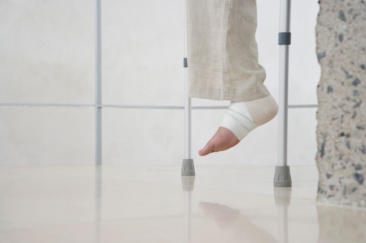 close-up picture of bandaged foot hovering over floor, next to crutches and a stone wall.