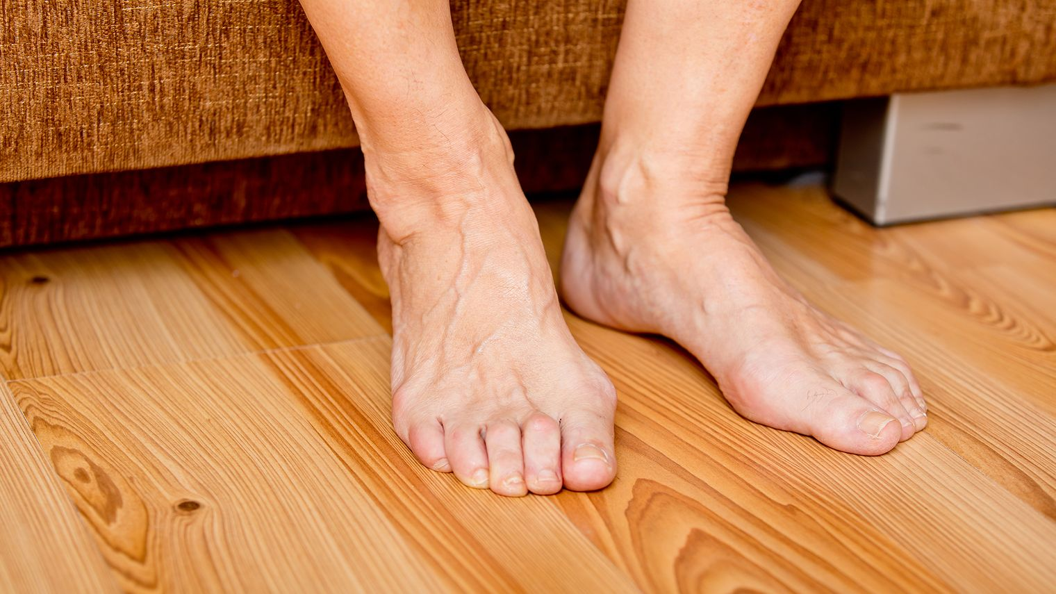 Close-up picture of two bare feet of a person sitting down planted on floor.