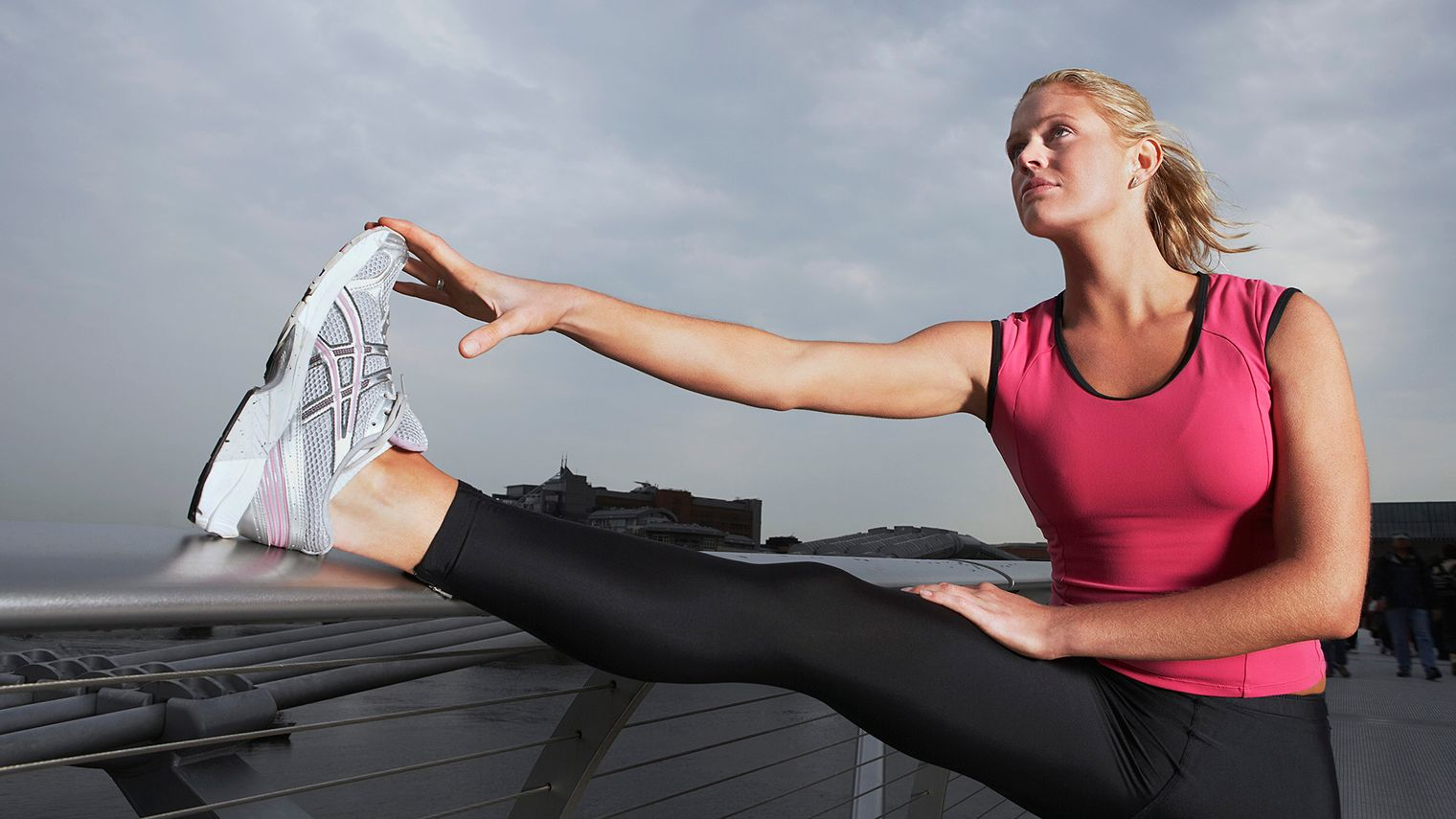Picture of female in sportswear stretching in exterior with foot on railing.