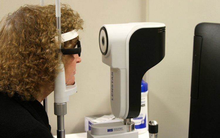 Picture of female patient using device to check her eyes.