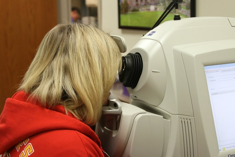 Blonde female young adult seen from the side using an eye examining machine.