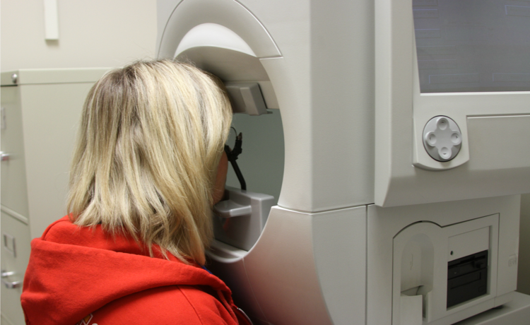 Blonde female young adult seen from the back with her head in an eye examining machine.