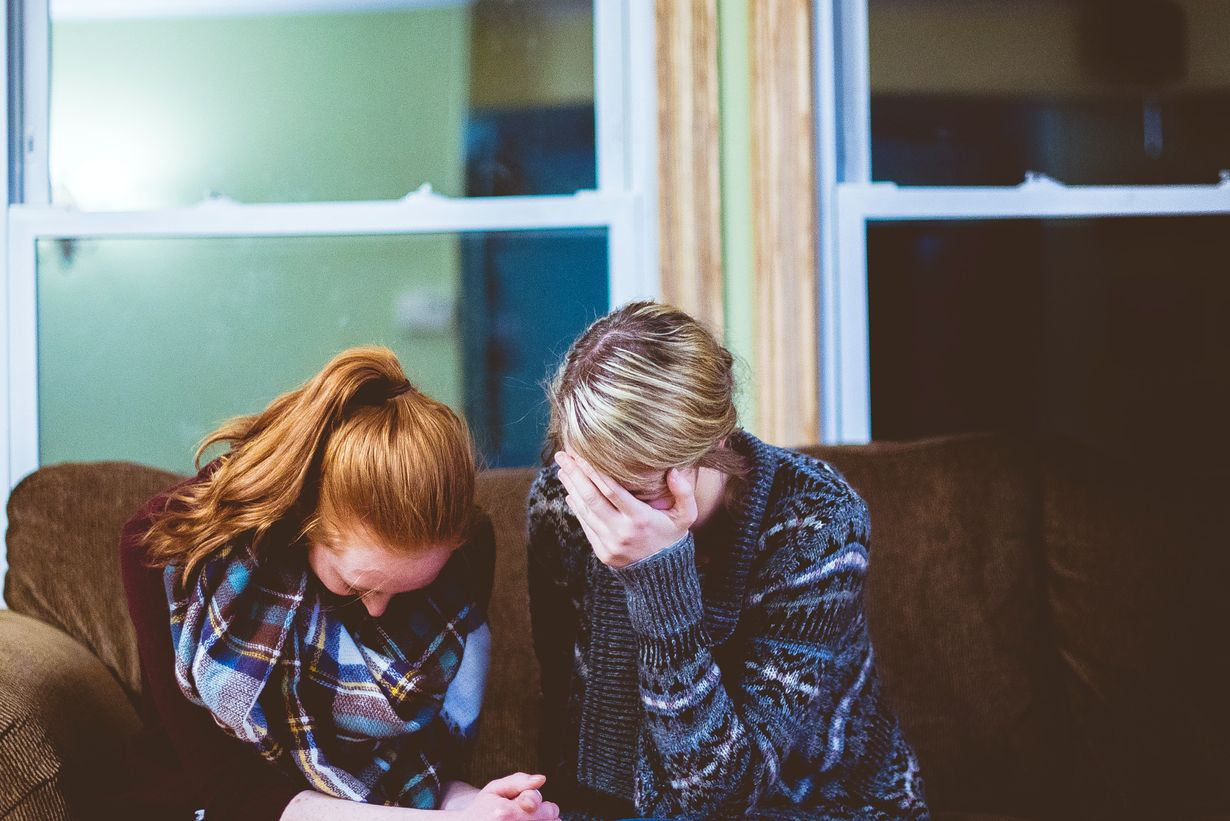 Photo of two women sitting on a couch praying for each other in the midst of a group counseling session.