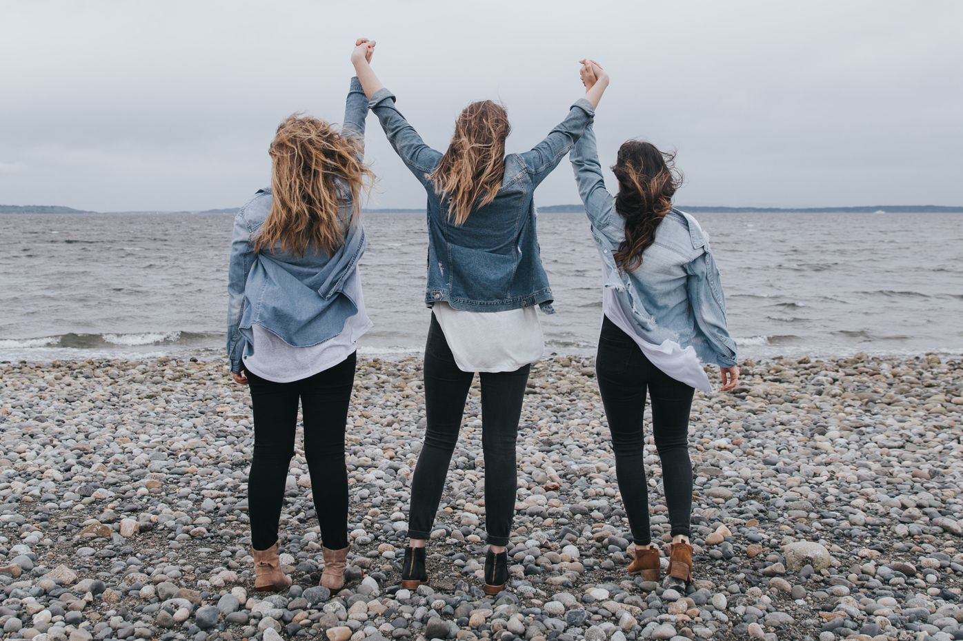 Photo of three women looking away towards a lake holding hands up in the air in support of each other after their group counseling session.