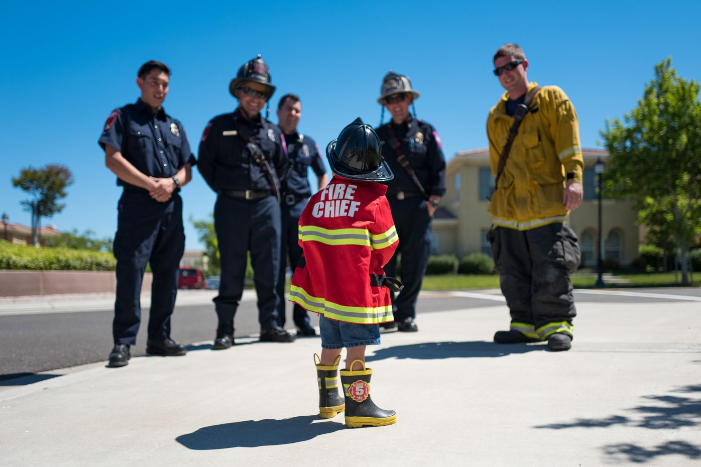 Photo of a small boy wearing a fireman costume looking at a group of adult firemen who think he is adorable.