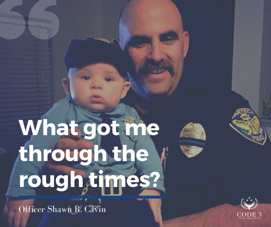 Photo of a law enforcement officer in his uniform holding his infant grandson who is also dressed as a police officer.