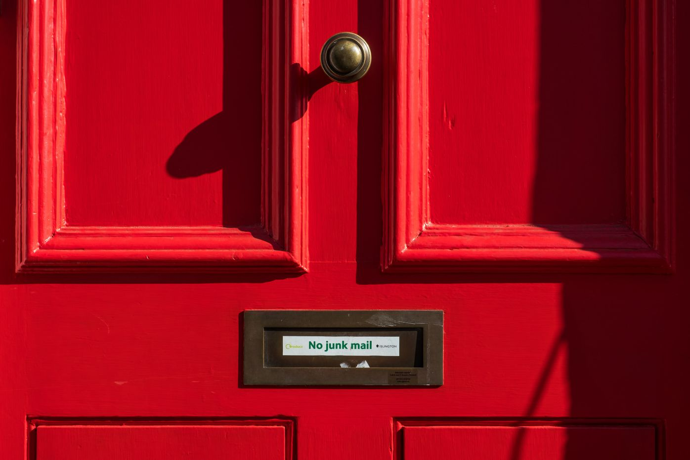 "Photo of a red door with a sign saying ""No junk mail"" over the mail slot showing that we do not send SPAM to your inbox with our newsletter."