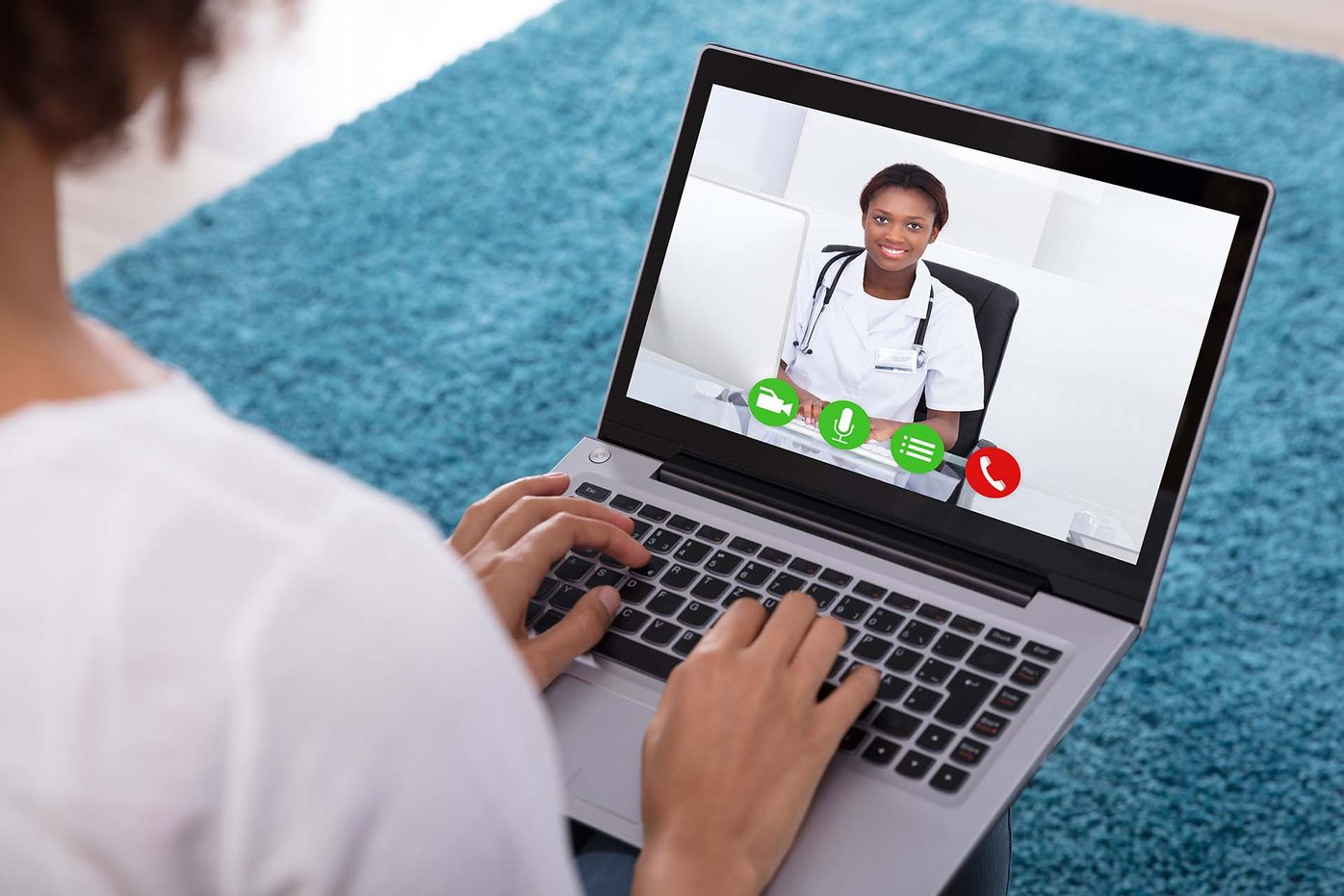 Woman on laptop watching female doctor on screen.