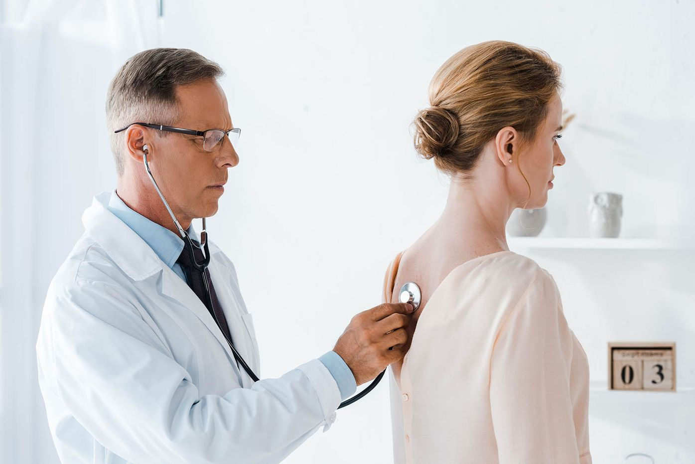 Male doctor using stethoscope on female patient's back.
